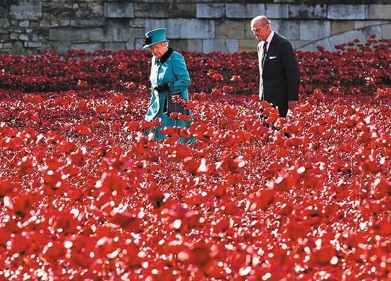 Королева Великобритании Елизавета II вместе со своим супругом, принцем Филиппом, во время посещения мемориала «Красные маки» музея замка Тауэр. 16 октября 2014 г.